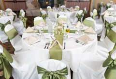 Table setup for a wedding with cloth napkins, silverware, chair covers, and centerpieces