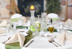 Place setting for a wedding with glasses, cloth napkins, silverware and party favors