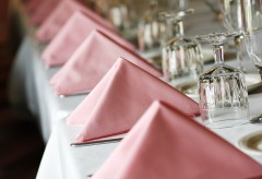 Place settings with pink cloth napkins and crystal glasses
