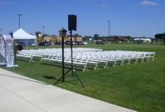 Outdoor wedding ceremony setup with lots of white chairs on the grass