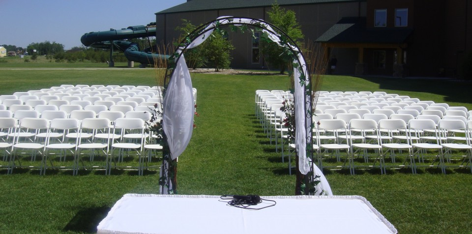 Outdoor wedding ceremony setup with an arch for the couple to stand under and white chairs for the guests