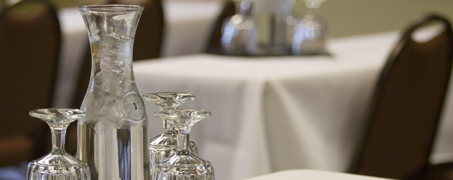 Water pitcher with ice and three glasses on a table